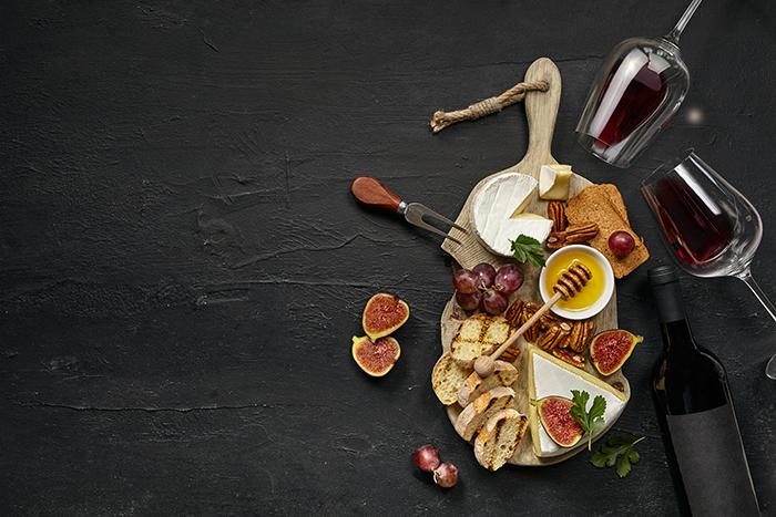 un tagliere di formaggi e calici di vino rosso, un ottimo abbinamento cibo e vino