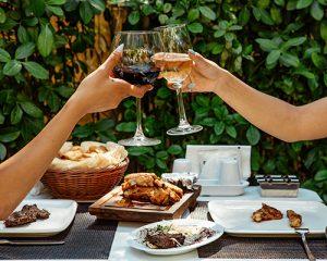 due persone sono pronte a bere davanti a una tavola imbandita, occasione per comprendere meglio abbinamento cibo vino