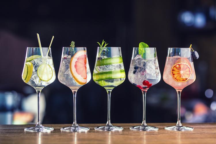 tanti gin diversi in bicchieri colorati, perfetti per la guida come riconoscere e bere gin di qualità