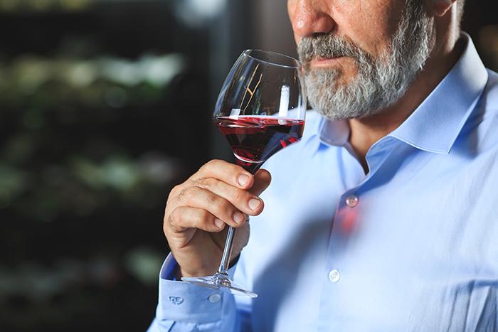 un sommelier assaggia un calice di vino rosso per comprendere il giusto abbinamento vino cibo